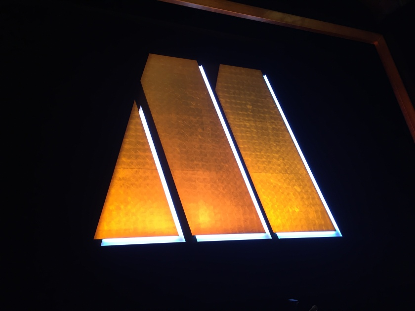 The large golden letter M logo for Motown, made up of a triangle then 2 thick diagonal bars, lit up on the black stage curtain.