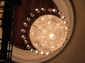 Ornate round chandelier light in the theatre auditorium, with lots of little lights sticking out all around it.