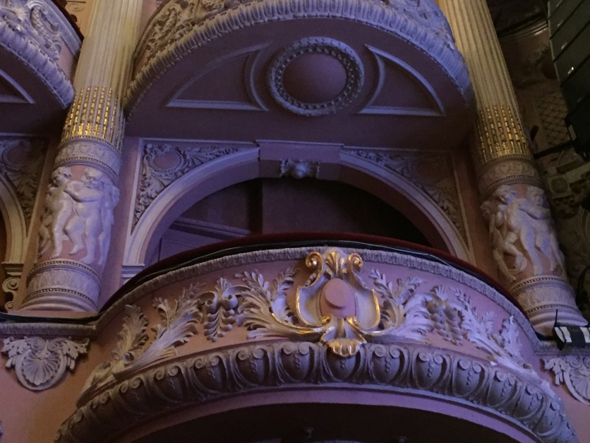 View from below of one of the curved balconies for the box seats in the auditorium, with ornate wing-like imagery embossed on the front of the balcony.