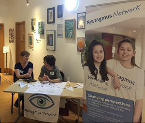 Sue Ricketts talking to a lady at the Nystagmus Network table ,with a tall poster next to it giving details of the charity.
