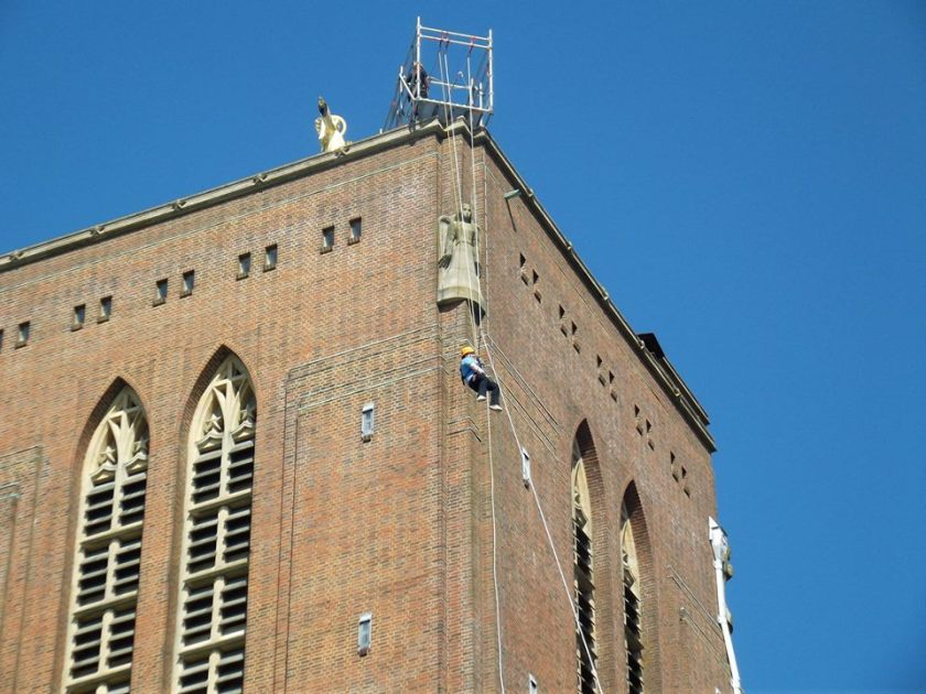 My friends abseiling off the tower of Guildford Cathedral. The line is coming out diagonally from the corner of the tower to the ground, so she's in mid-air, not touching the building.