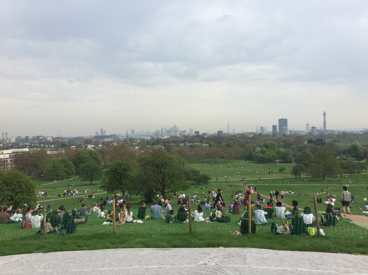 London skyline viewed from Primrose Hill. Lots of people are sitting on the grassy hill stretching down into the park below, while in the distance is the London skyline, including iconic sights like the Shard, BT Tower and London Eye.