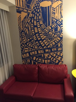 2 seater leather sofa in my hotel room. Behind it on the wall is a tall blue and yellow stylised artwork, illustrating cars driving on winding roads, on multiple levels, in amongst skyscrapers.