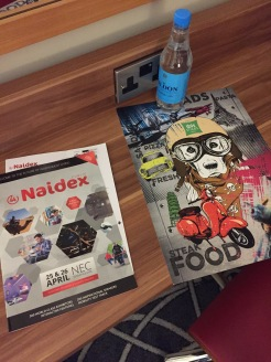 Naidex show guide, hotel food menu and a bottle of water on the desk in my hotel room. The menu has a big drawing of a dog riding a motorbike on the cover.