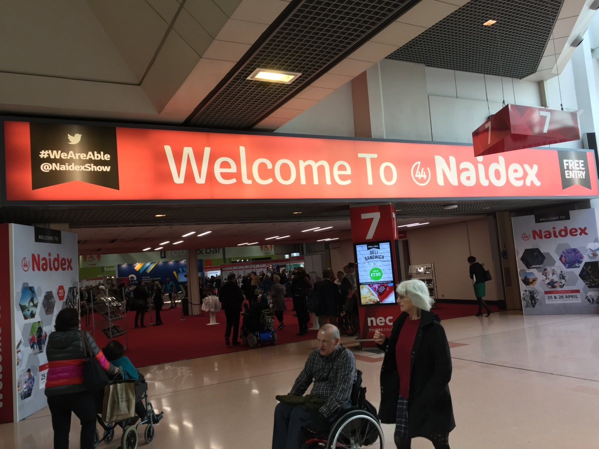 Entrance to Naidex show. Above a wide entrance to the hall is a long red sign, on which is large white text saying Welcome To Naidex. White text on a black panel to the left shows their Twitter name, Naidex Show, and the hashtag We Are Able. White text on a black panel on the right says Free Entry.