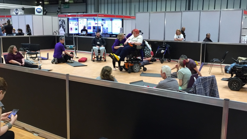 People on mats and in wheelchairs doing yoga at Naidex while others watch