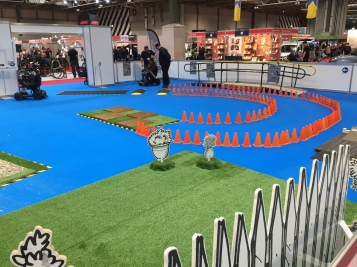 Right side of the Mobility Test Track at Naidex. On a large blue floor are 2 small speed bumps leading to a curved path created by cones, leading a section of uneven paving. There is also a large patch of fake grass to try driving on.