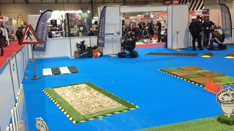 Left side of the Mobility Test Track at Naidex. On a large blue floor are obstacles including a small mockup of a zebra crossing, a section of gravel, and a section of uneven paving.