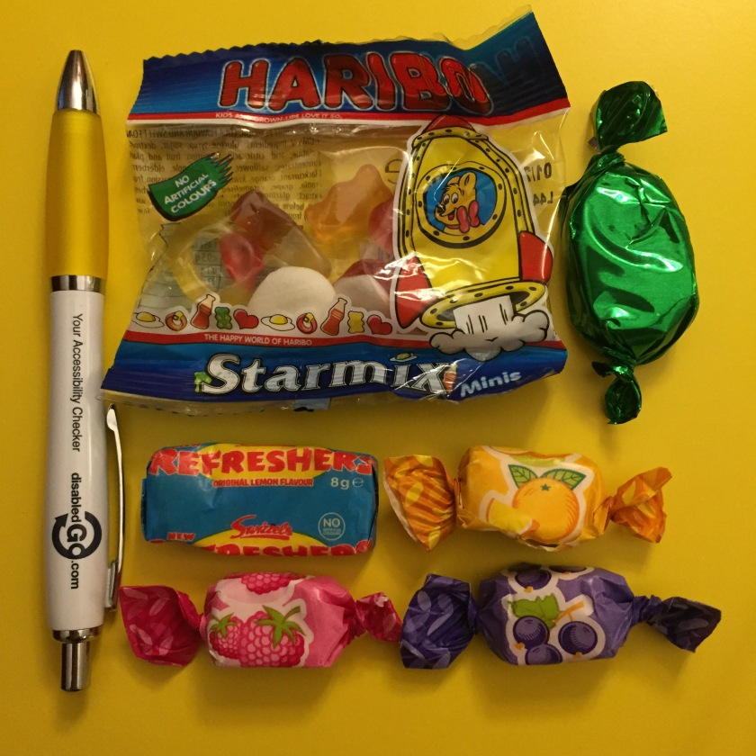 A pen from Disabled Go, plus a selection of sweets, including a small bag of Haribo Starmix, a Freshers sweet, a chocolate sweet, and 3 fruit flavoured sweets in orange, strawberry and blackcurrant.