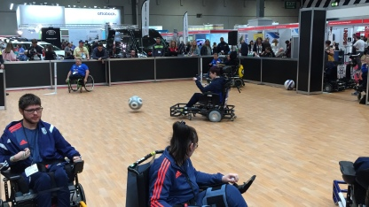 Powerchair Football at Naidex, with the ball travelling towards the goal, having been kicked by one powerchair user.