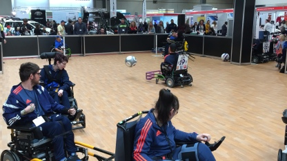Powerchair Football at Naidex. The ball has been launched into the air as it travels towards the goal.