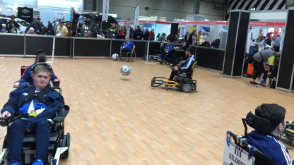 Powerchair Football at Naidex. The powerchairs have a an attachment made of thick bars on the front, which is used to kick the ball.