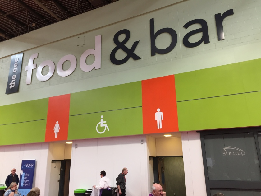 Food and toilet signs on the wall. The words Food & Bar are in massive letters on the top section of the wall. Below this, above the 2 toilet entrances, are large orange panels with large white figures of a woman and a man respectively. In between, on a green section of wall, is the disability wheelchair symbol.