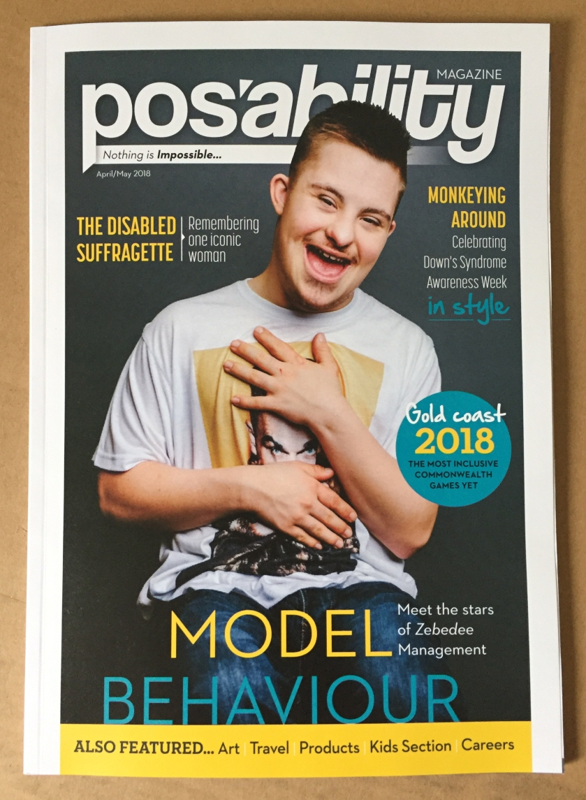 PosAbility Magazine, with a male disabled model on the front. He is smiling and wearing a white t-shirt with a face on the front, but the model's hands are across his chest so we can only see the eyes of the face on the t-shirt.