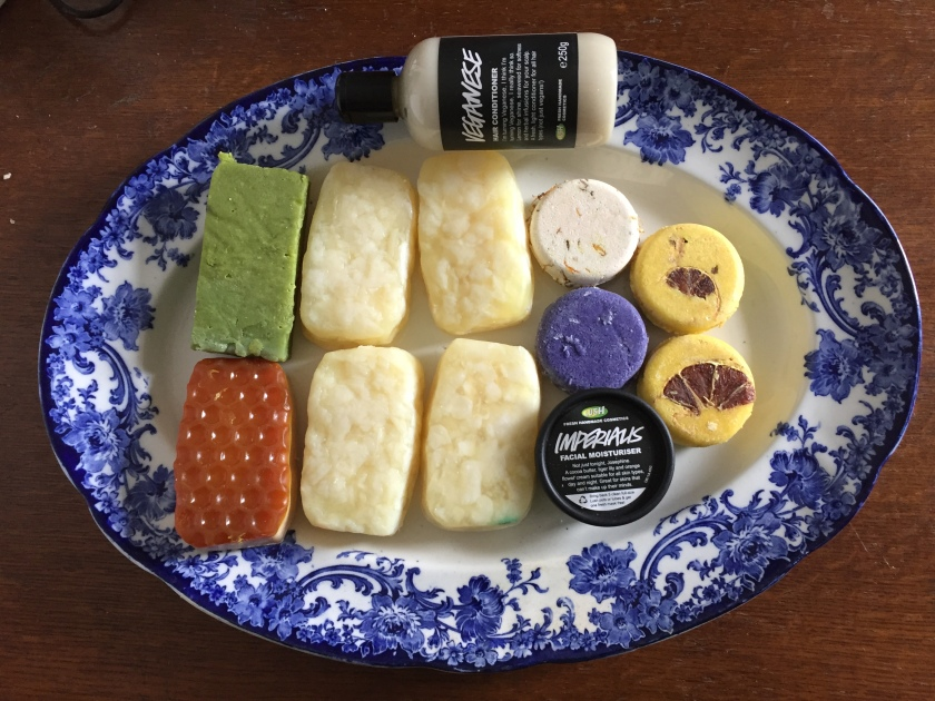 Large ornately decorated plate with the contents of our Lush order - 6 soap bars (including 4 Bohemian bars), 4 shampoo bars (including 2 Montalbano bars), a tub of Imperialis moisturiser, and a bottle of Veganese hair conditioner.