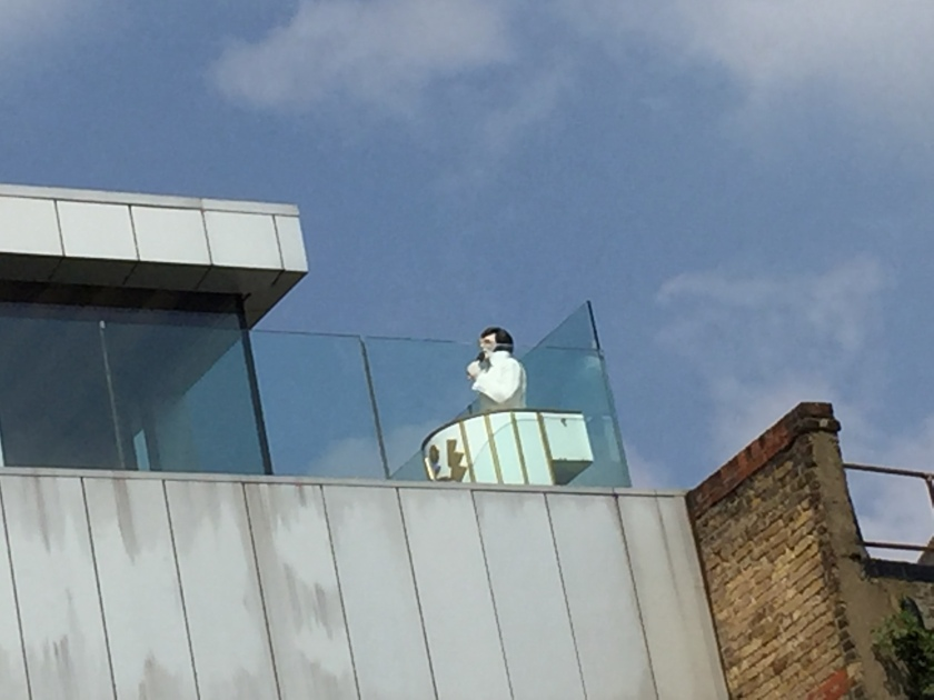 Model of Elvis Presley dressed in white and singing, on top of a building by the Grand Union Canal.