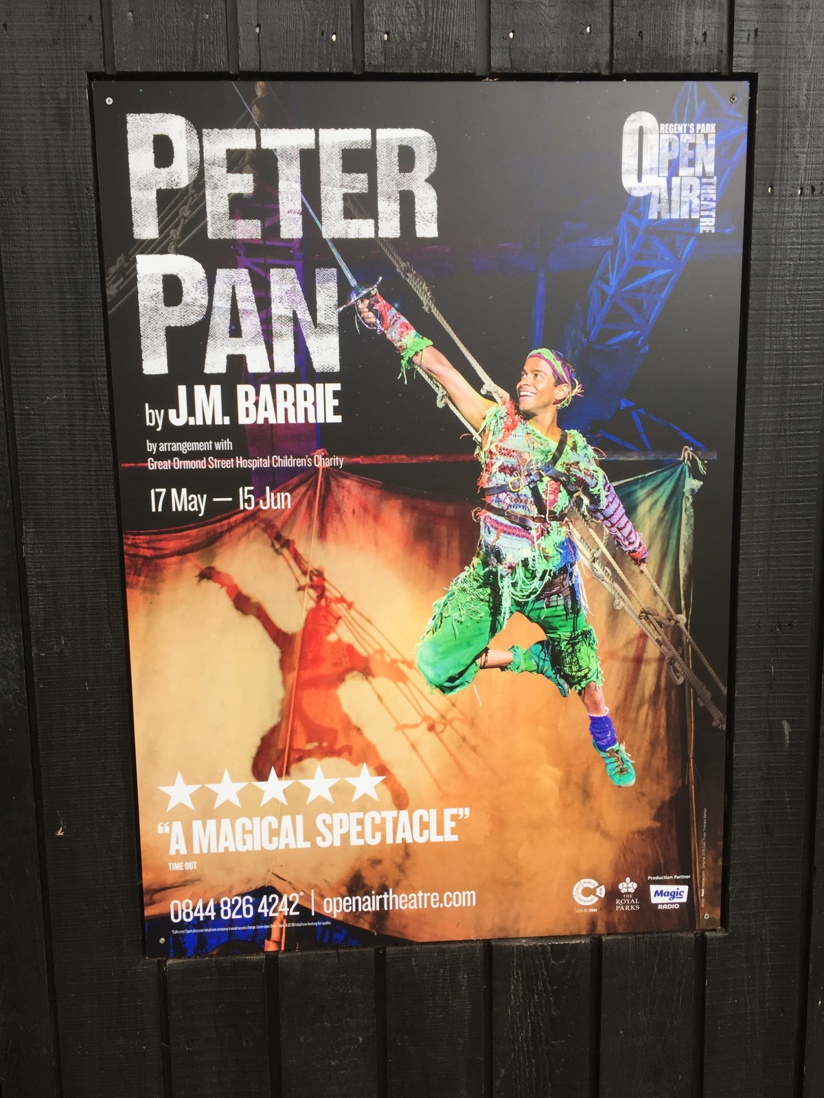 Poster for Peter Pan by J.M. Barrie, at the Regent's Park Open Air Theatre from 17 May to 15 June. Includes an image of Peter Pan flying and smiling, holding his sword up in front of him, with the sail of Captain Hook's boat behind him.