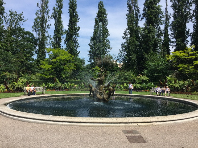 Large circular pool with a fountain statue in the middle. The statue is made of 3 figures - one male figure in the centre looking up and spraying a jet of water high into the air, and then 2 female figures either side of him, spraying water out in various directions around them.