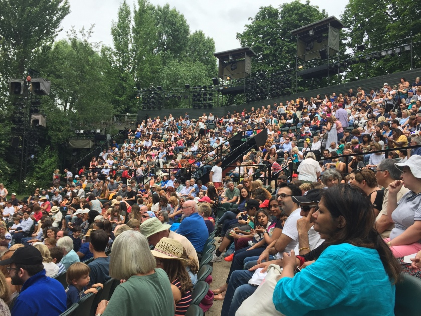 Audience at the Open Air Theatre, sitting in a curved formation around the front of the stage, each row of seating a step higher than the row before.
