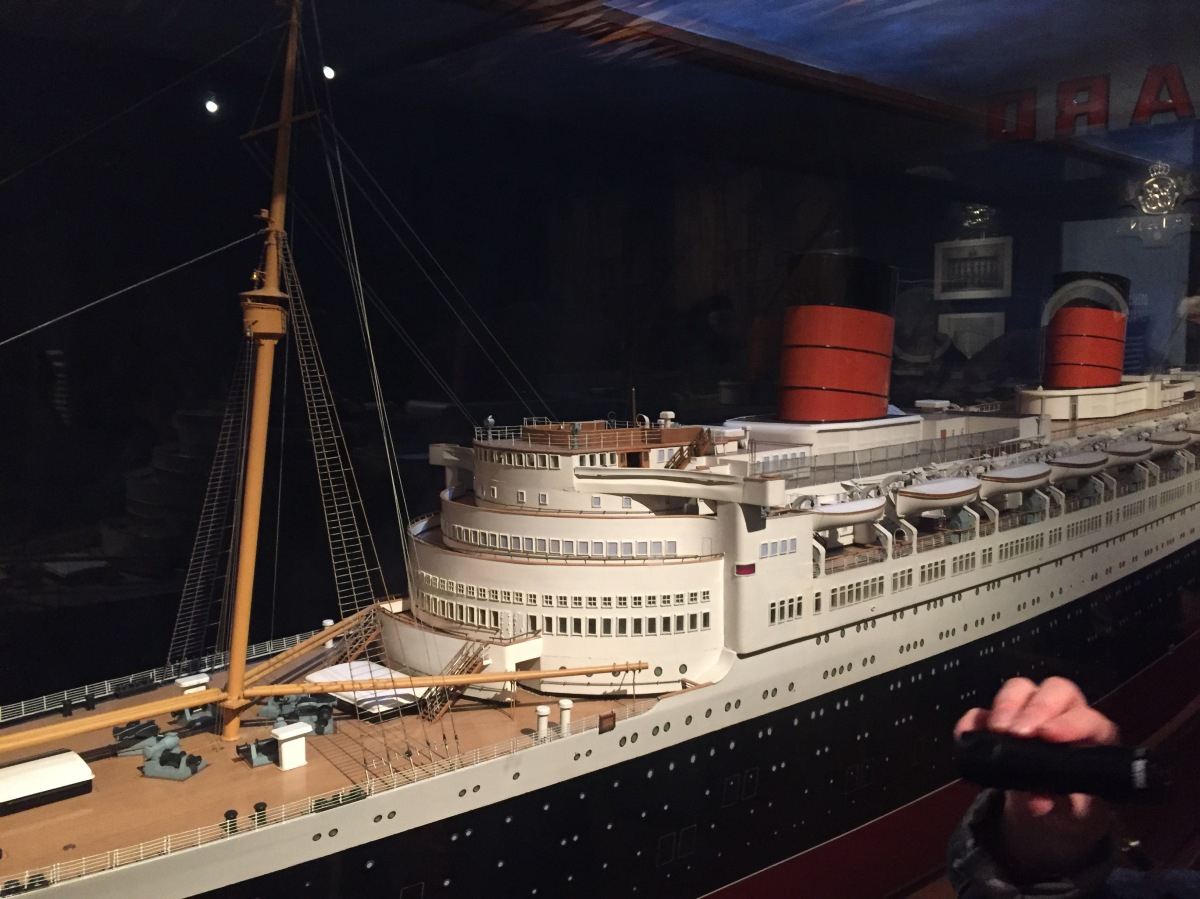 A very long and highly detailed model of the Queen Elizabeth Cruise Liner. The ship has a black base, with white buildings on the top, and details including the large mast down to the small lifeboats, windows and railings are all reproduced in the model.