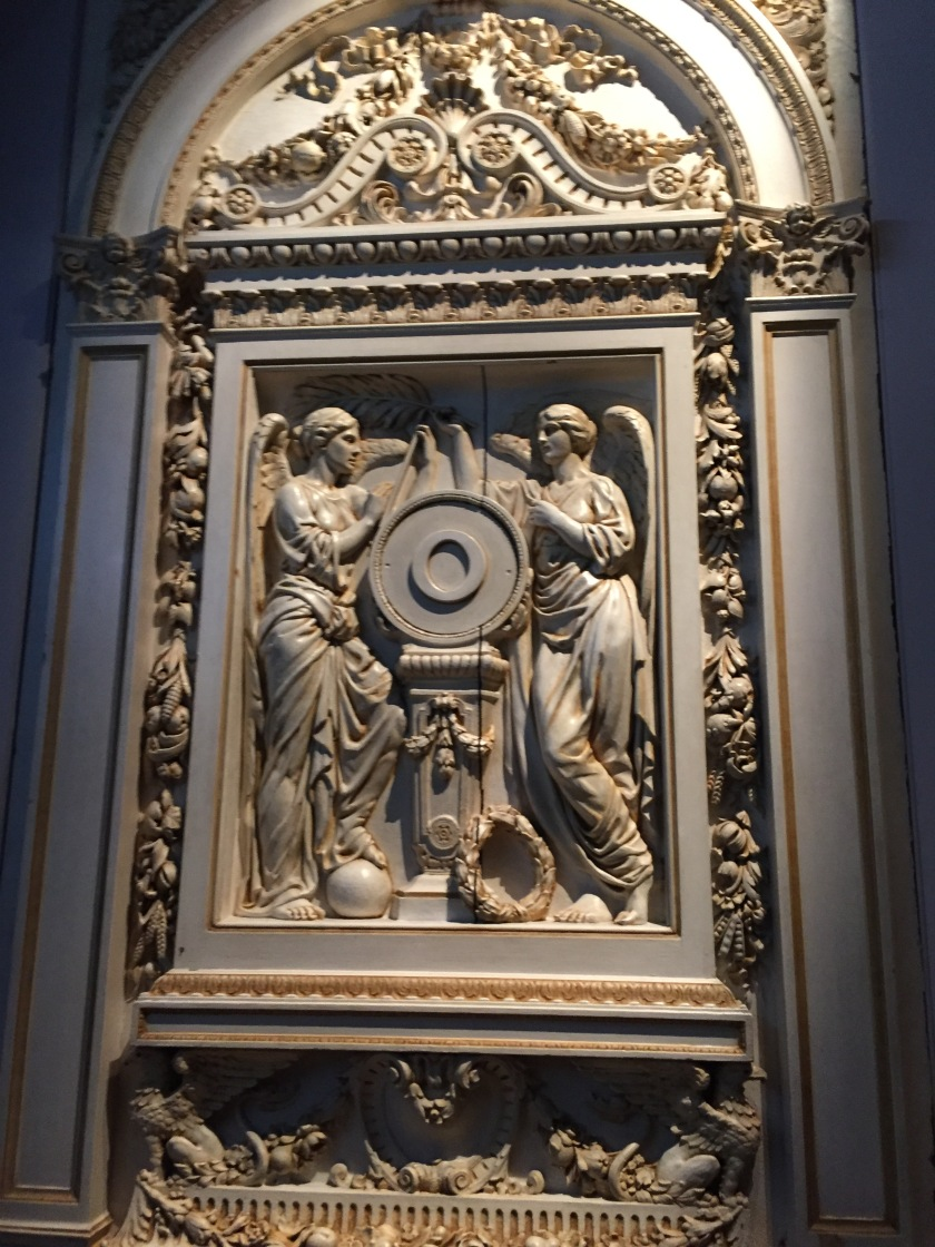 Very ornate sculpted artwork on the wall, featuring 2 angel figures by a circular wheel on a plinth in the centre.