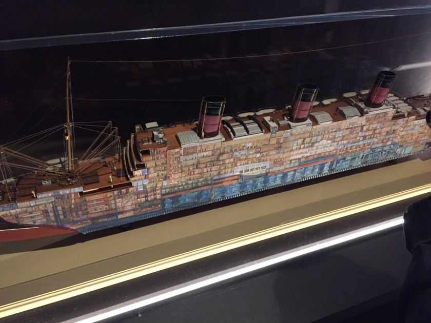 Large cross section model of an ocean liner. The side of the boat has small images of all the rooms on that side of the vessel, including items of furniture and people in the rooms.