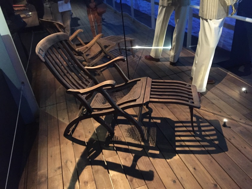 Reclining wooden deckchair, with slats in the wood on the back and leg rest.