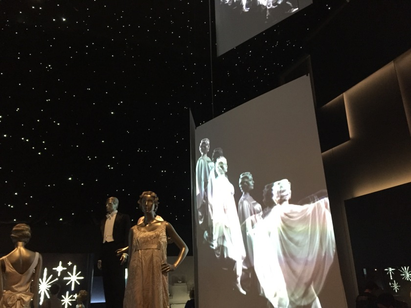 Below a black ceiling covered in stars to look like the night sky, a large screen shows black and white footage of ladies in long dresses descending a staircase. In front of the screen are mannequin models of a man in a smart suit and a woman in an elegant dress.