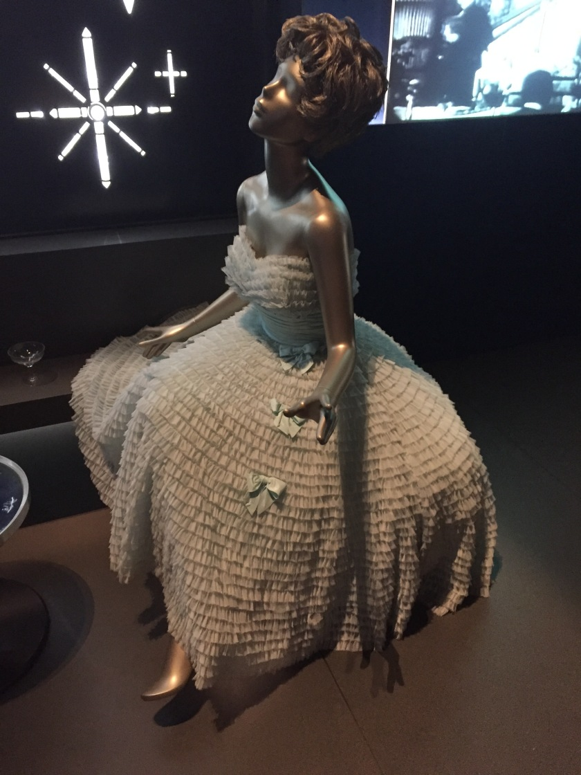 Mannequin wearing a white dress that spreads out widely at the bottom, covered in many layers of ruffles and adorned with a few bows.