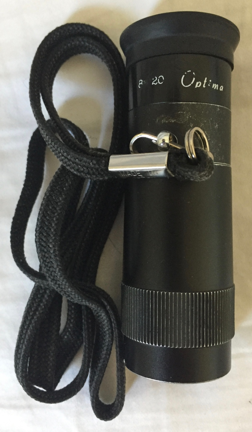 My monocular, a small black telescope with a rubber ring attached to the eyepiece end for comfort, and a cord attached on the side so you can hang it around your neck.