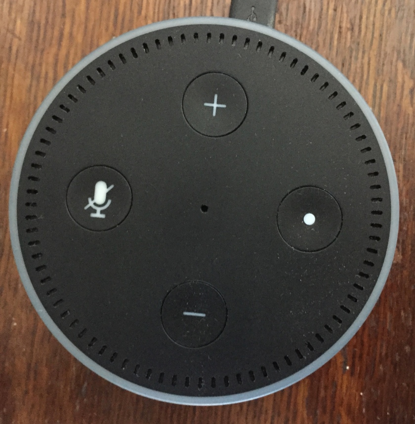 Amazon Echo Dot - Small round black machine with a small speaker grill and light encircling the outer edge on top. 4 buttons are on the front - plus and minus volume buttons at the top and bottom, a mute button on the left, and a control button with a dot on it on the right.
