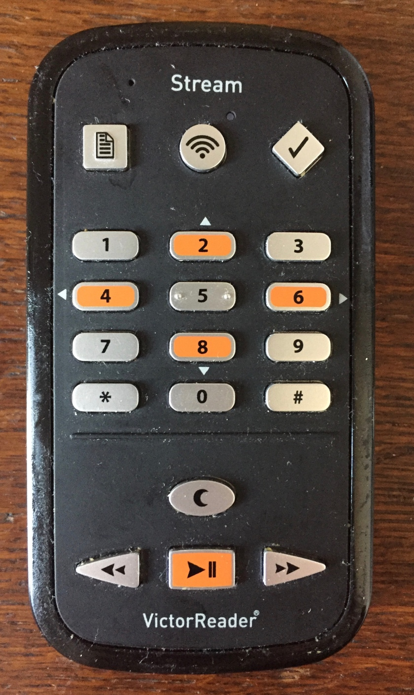 Victor Reader Stream player, a black rectangular device with curved corners. The centre of the device is a number keypad, with 2 dots on the 5. Most keys are silver, but 2, 4, 6 and 8 are orange. At the top are square, circular and diamond shaped buttons. At the bottom is a square orange play button with triangular rewind and fast forward buttons either side, and just above the play button is a silver oval shaped button.