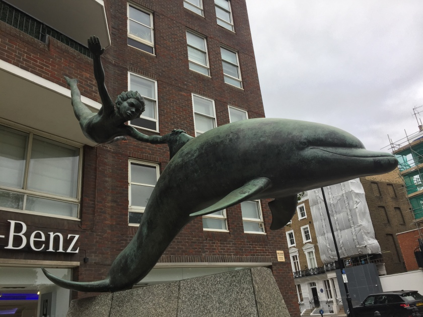Statue of a dolphin swimming, with a boy clinging on to its upper fin as he floats in mid-air, giving the impression that the dolphin is moving at speed.