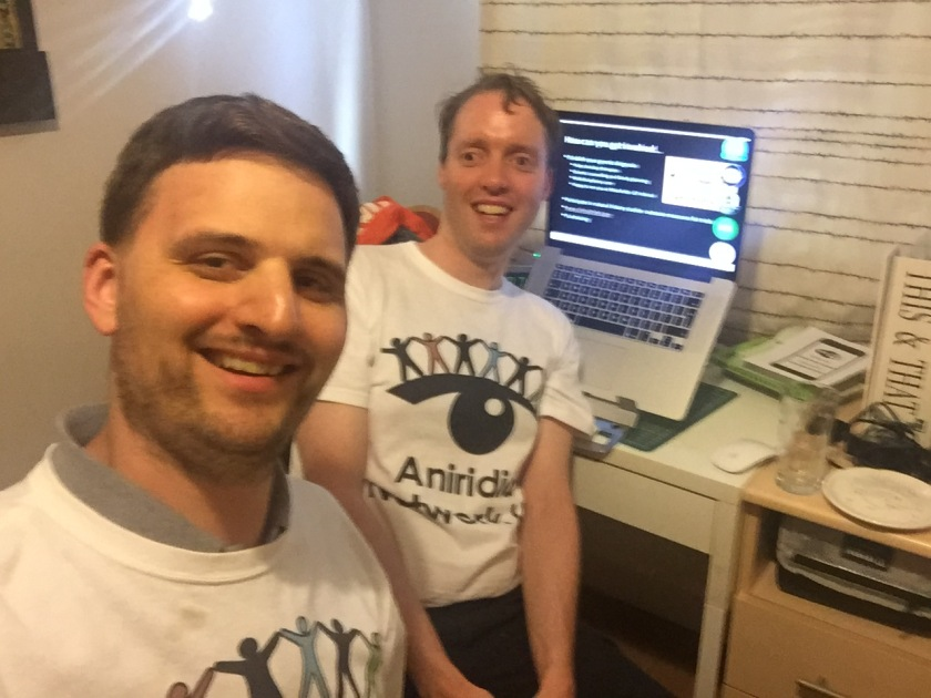 Glen and James smiling and wearing white Aniridia Network t-shirts, while sitting in front of a laptop computer on which there is a presentation slide from a live webinar they're watching.