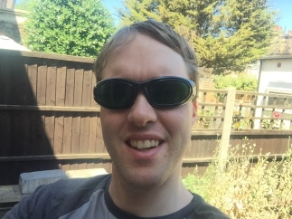 Selfie in my sunny back garden, in which I'm smiling and wearing my green tinted sunglasses.