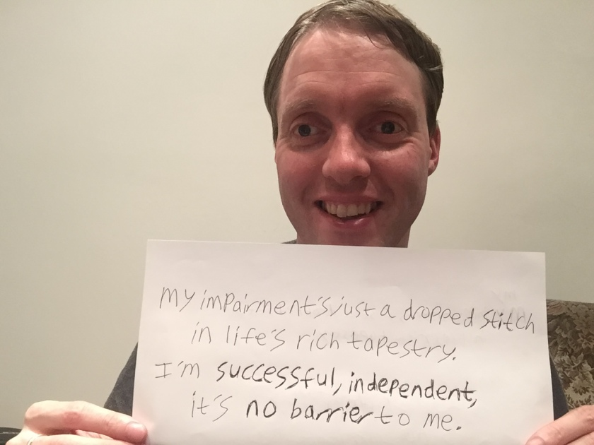 "Me smiling and holding up a piece of paper showing a handwritten quote I've come up with. It says: ""My impairment's just a dropped stitch in life's rich tapestry. I'm successful, independent, it's no barrier to me."""