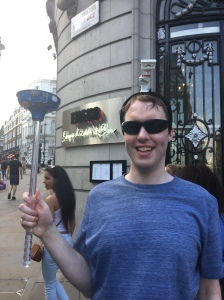 Glen outside on a busy London street, smiling and wearing his sunglasses, with a small model toilet on his head and a large plunger in his hand.