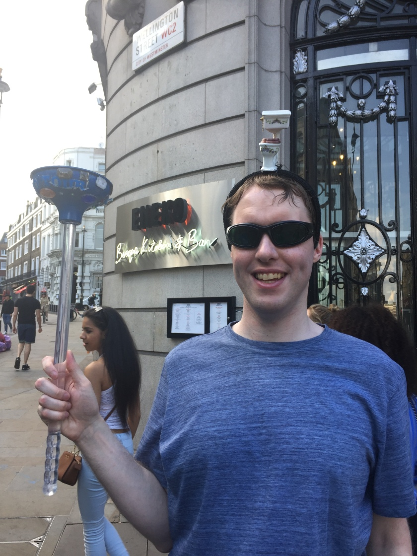 Photo of me outside on a busy London street, smiling and wearing my sunglasses, with a small model toilet on my head and a large plunger in my hand.