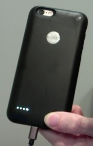 Rear of black iPhone case. Pressing a button on the bottom right reveals 4 small lights in a row on the left, to show the case is fully charged. Below this, the charging cable is plugged into the bottom of the case, in the same central position as the iPhone charging port is located inside the case. At the top of the case, a hole is left open for the camera and flash.