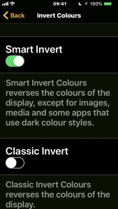 iPhone screenshot of the Invert Colours menu, with options for Smart Invert, where it inverts everything except media like photos and videos, and Classic Invert, where it inverts everything.