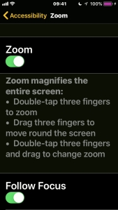 iPhone screenshot of the Zoom menu, explaining the gestures - double-tap 3 fingers to zoom, drag 3 fingers to move round the screen, and double-tap 3 fingers then drag to change teh zoom.