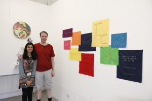 Glen and Nihan standing next to her artwork made up of pieces of coloured fabric on the wall, each a different colour and size, and either square or rectangular in shape, and each containing a message in braille.