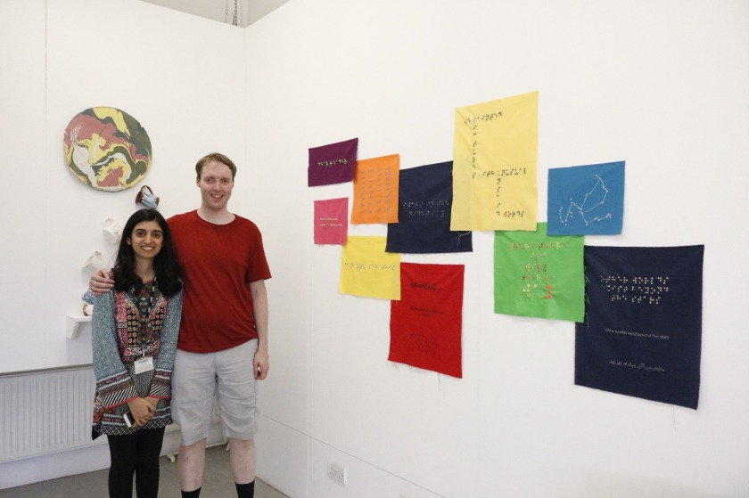 Me and Nihan standing next to her artwork made up of pieces of coloured fabric on the wall, each a different colour and size, and either square or rectangular in shape, and each containing a message in braille.