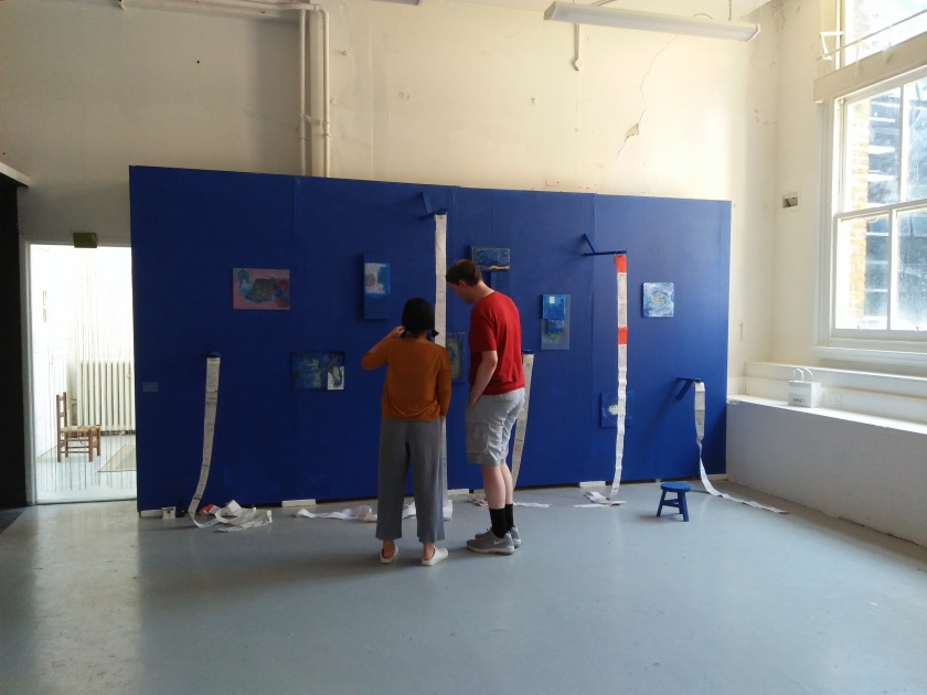 Me talking to a student in front of their artwork, which spans the length of a blue coloured wall, on which are placed various small colourful pictures, and narrow lengths of paper hanging down, including receipts stuck together in a continuous chain.