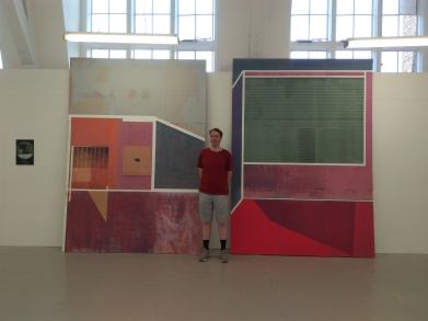 Me standing in front of a very large artwork, considering of large colourful panels, mainly squares and rectangles, but some have diagonal edges on one side.