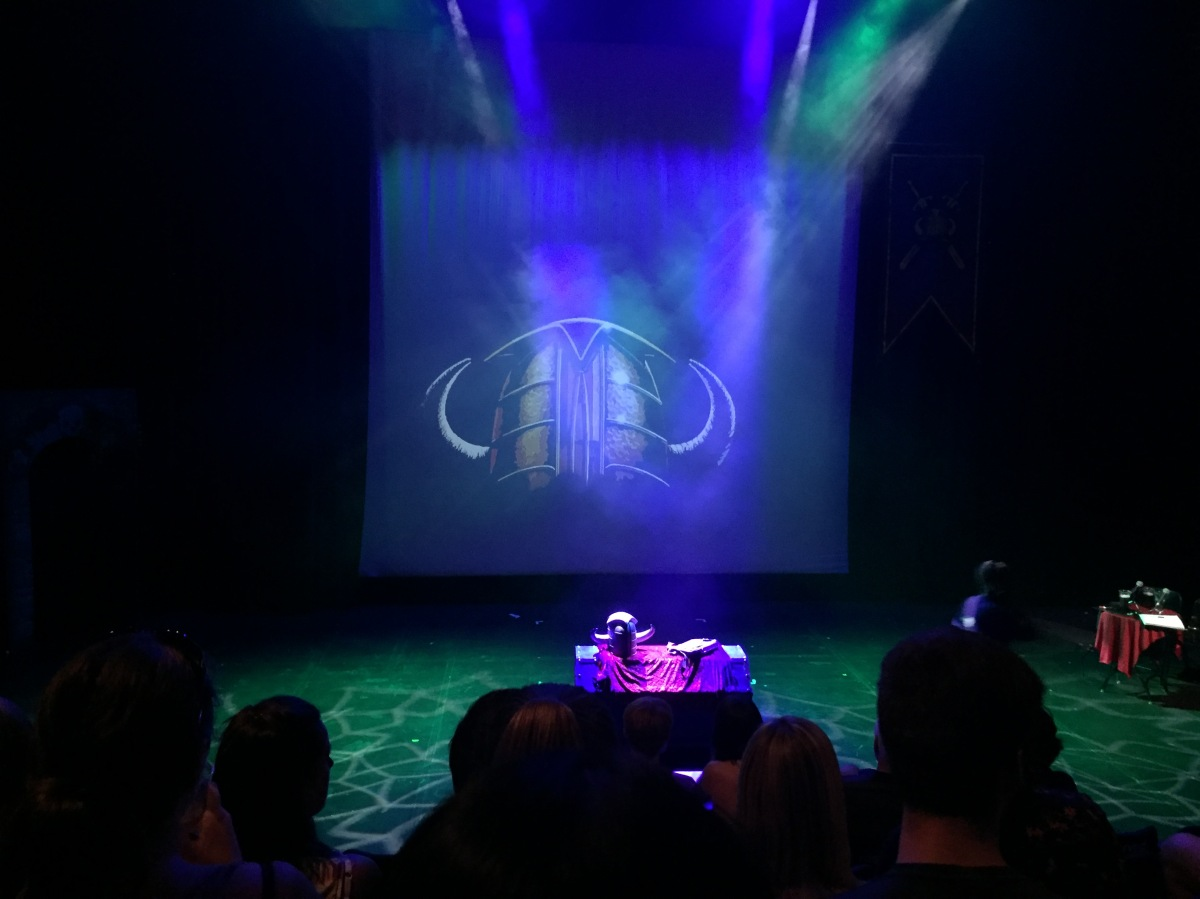 Stage for Knightmare Live. Surrounded in darkness, the large back screen is filled with a large image of the dungeoneer's helmet, which goes down far enough in the front to cover the eyes, and has 2 horns curving inwards on each side. On a table on the stage is an actual dungeoneer's helmet plus a knapsack for carrying items.