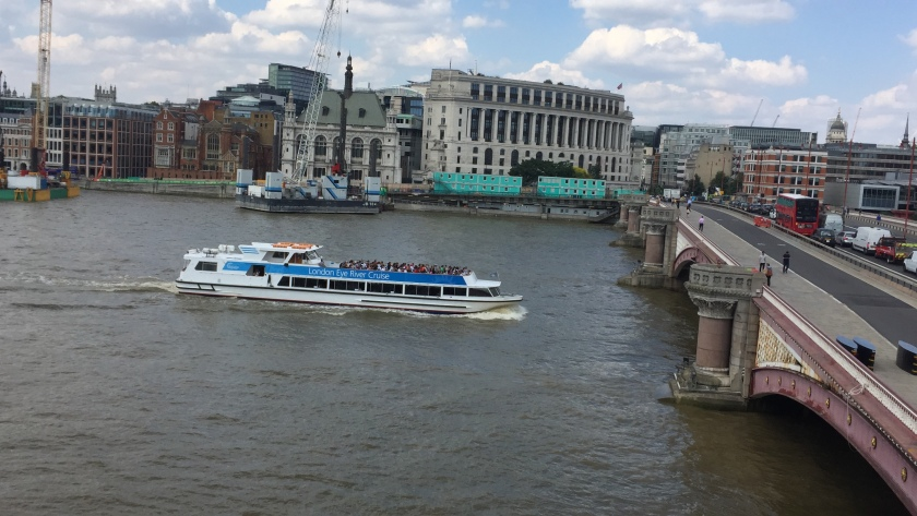 A long white and blue tourist boat passing under Blackfriars Bridge