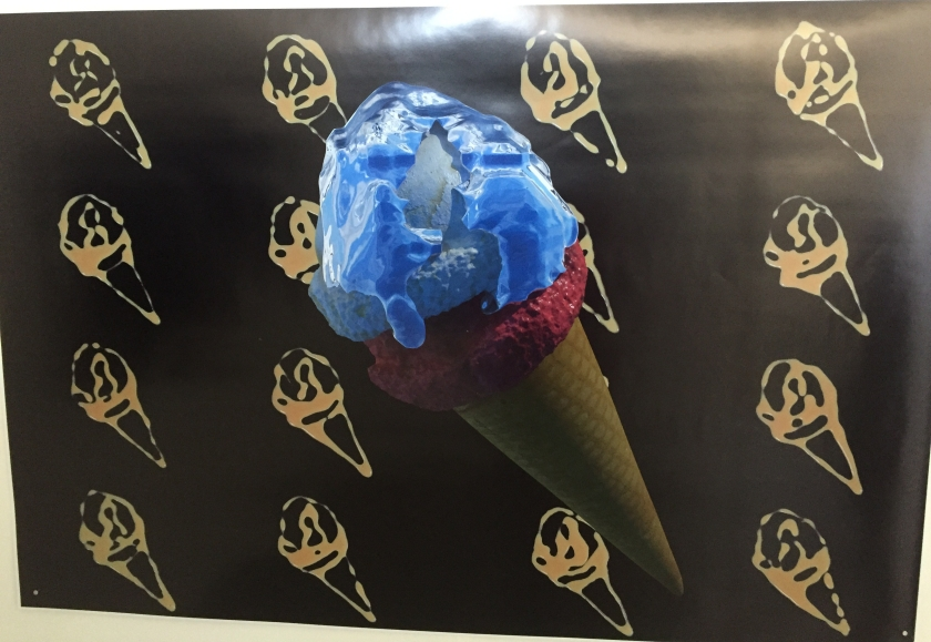 An artistic print of a large ice cream cone with blue and white ice cream on the top, against a background of repeating ice cream silhouettes in a golden colour against a black background.