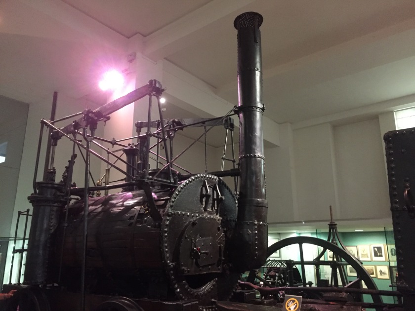 A large steam engine with a very tall chimney.