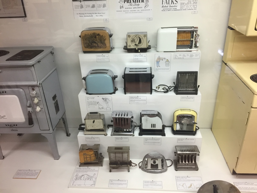 4 shelves containing 14 toasters in a variety of different designs.